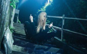 夜、階段に座って中指を立てている多田さん